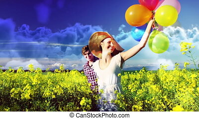 Couple with balloons walking in the field