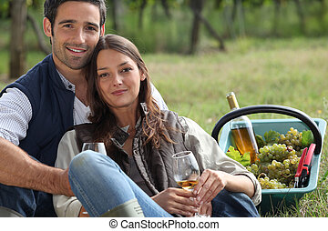 Couple with basket of grapes and wine