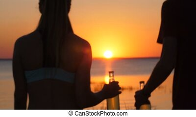 Couple with beer bottle walking on beach at sunset