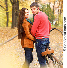 Couple with bicycle in autumn park