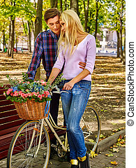 Couple with bicycle in autumn park.