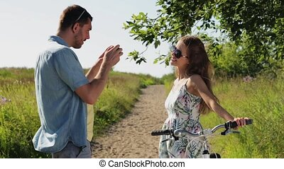 couple with bicycle photographing by smartphone