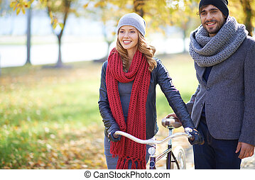 Couple with bike walking in autumn