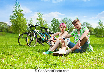 Couple with bikes - Beautiful young couple sitting on the ...
