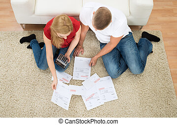 Couple With Bills And Calculator - High Angle View Young...