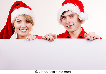 Couple with blank empty banner board. Christmas