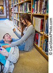 Couple with books at the library aisle