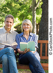 Couple with books on park bench