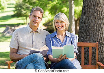 Couple with books sitting on bench
