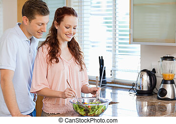 Couple with bowl of salad in the kitchen