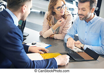 Couple with car dealer in the showroom
