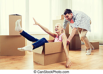 couple with cardboard boxes having fun at new home - home,...