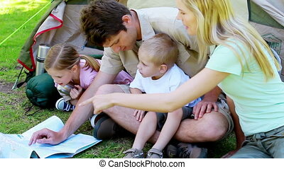 Couple with children looking a map