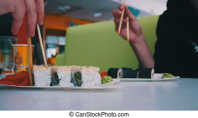 Couple with Chopsticks Takes Sushi from a Plate in a Japanese Restaurant