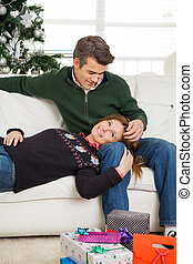 Couple With Christmas Gifts On Floor Relaxing On Sofa