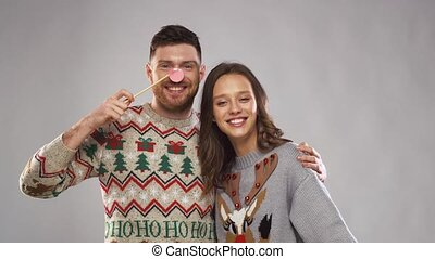 couple with christmas party props at photo booth -...