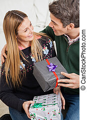 Couple With Christmas Presents Looking At Each Other