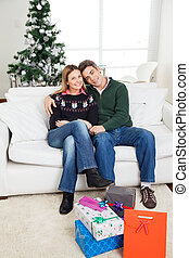 Couple With Christmas Presents On Floor