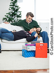 Couple With Christmas Presents Relaxing On Sofa