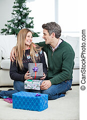 Couple With Christmas Presents Sitting On Floor