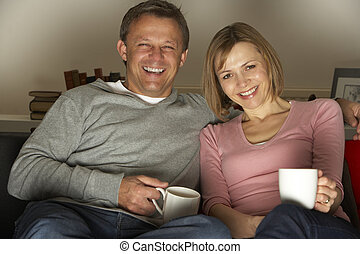 Couple With Coffee Mugs Watching Television