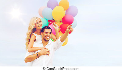 couple with colorful balloons at sea side