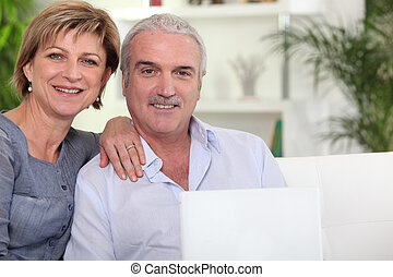 Couple with computer on couch