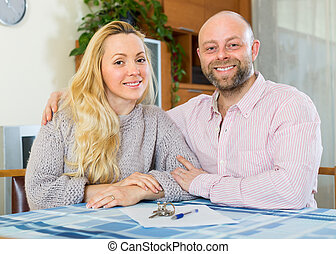 Couple with contract for buying apartment