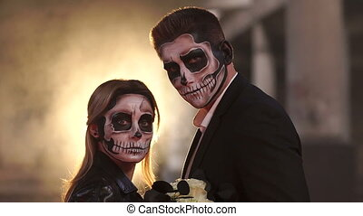 Couple with dark skull makeup on the background of burning fire and smoke.