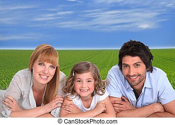 couple with daughter lying cross-armed in green setting