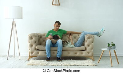 Couple with digital devices relaxing on the couch