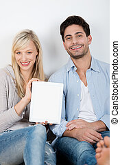 Couple With Digital Tablet Sitting Against Wall