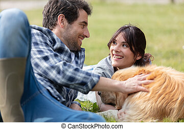 couple with dog lying in a field