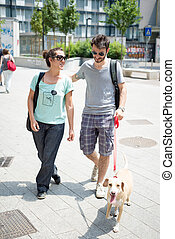couple with dog walking in the street