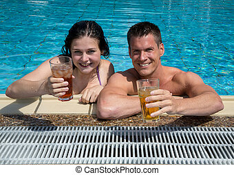 Couple with drinks in the sund at pool - Couple drinking...
