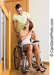 couple with female in wheelchair near door