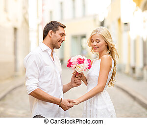 couple with flowers in the city - summer holidays, love,...