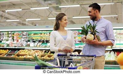 couple with food in shopping cart at grocery store - sale,...