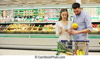 couple with food in shopping cart at grocery store