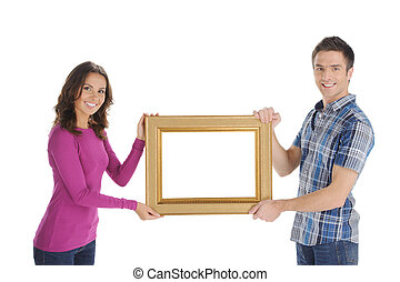 Couple with frame. Beautiful young couple holding a picture frame and smiling at camera while isolated on white