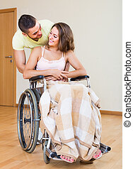 couple with girl in wheelchair near door