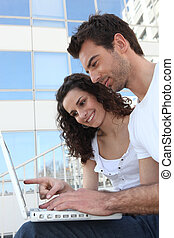 Couple with glass building in front of computer