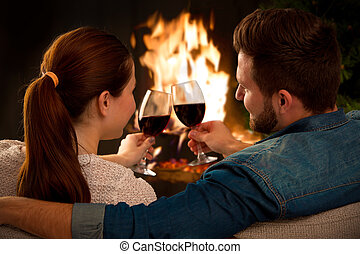 Couple with glass of wine at fireplace