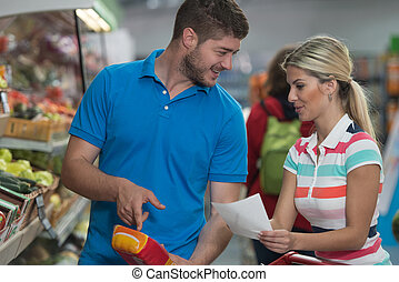 Couple With Grocery List In Supermarket - Beautiful Young...