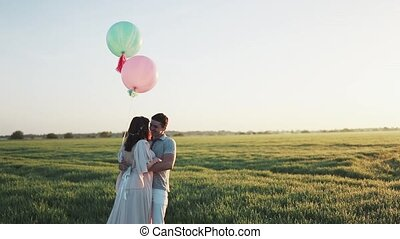 Couple with helium balls walking in a apple garden and holding hands at sunrise. Filmed in slow motion