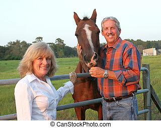 Couple With Horse - A handsome farm couple posing with their...