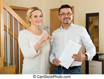 Couple with keys and documents