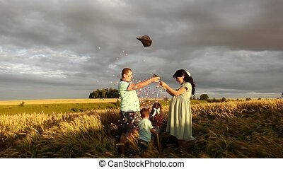 Couple with kids stand in a wheat field and pop air balloon to know the gender of future baby