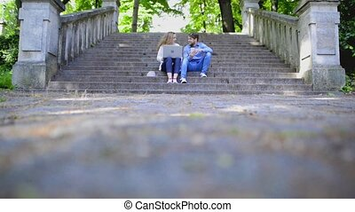 Couple with laptop and smartphone sitting on stairs in town.