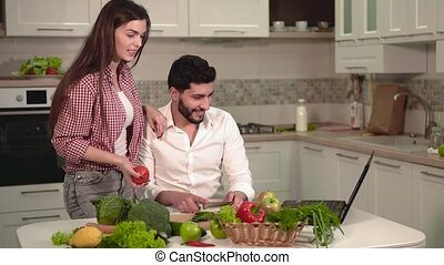 Couple with Laptop During Meal Prep - Handsome dark-haired...